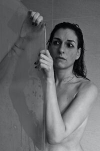 Scared woman in the shower peering out remembering what verbally abusive boss said.